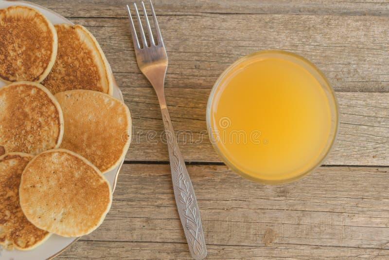 Frukostera med pannkakor och orange fruktsaft med metallgaffeln på en trätabell royaltyfria bilder
