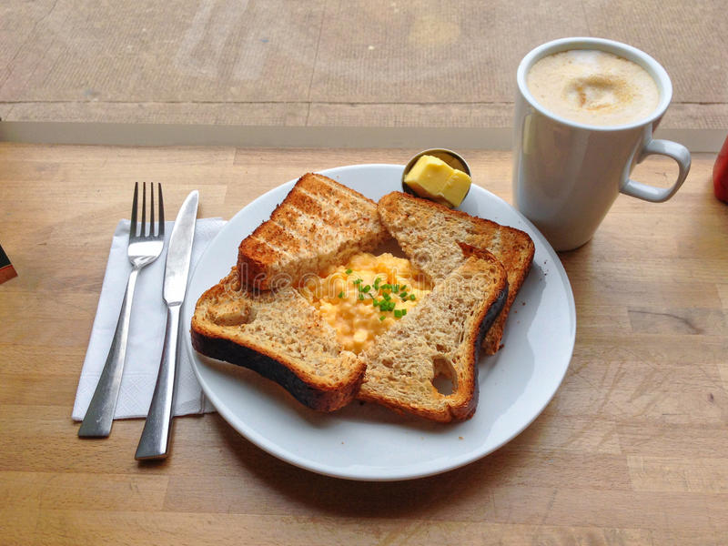 Frukostera med rostat bröd, ägg och kaffe royaltyfri foto