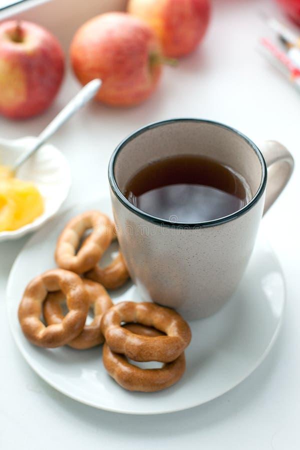Frukostera med varm te, kakor och honung Sund hem- frukostcincept Stäng sig upp av en kopp te med kakor på den vita maträtten arkivbild