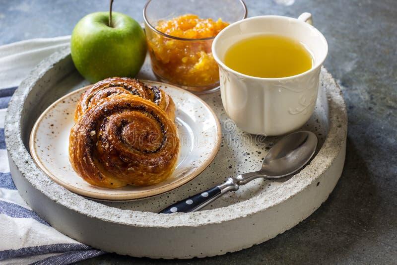 Frukostera på magasinet som tjänas som med grönt te, orange driftstopp och bullar royaltyfria foton