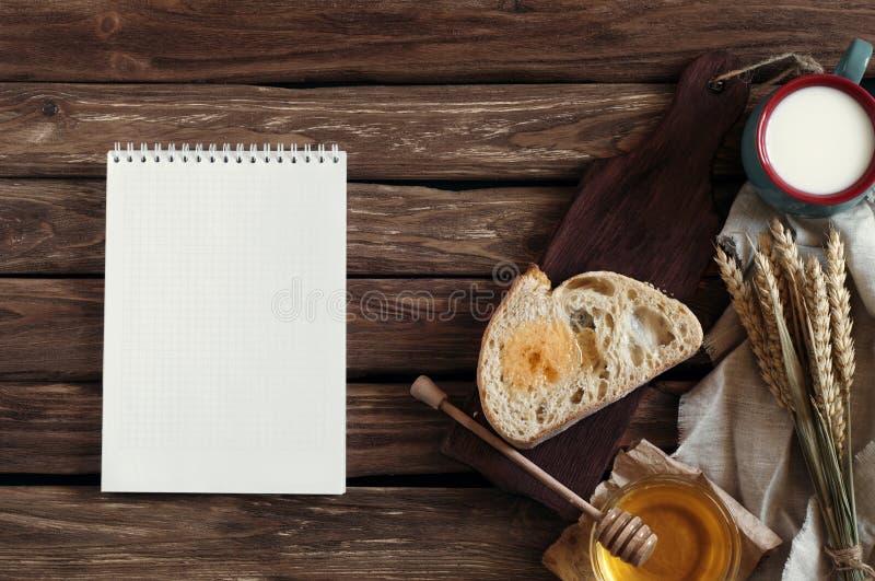 Frukostera a-skivan av bröd, honung, mjölka, och vete gå i ax på en ol royaltyfri bild