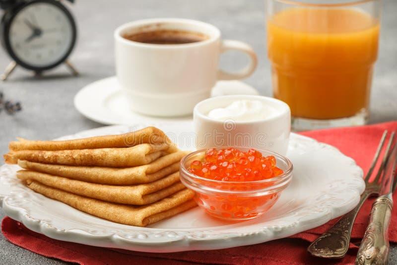 Frukostera tunna pannkakor med den röda kaviaren i den vita bunken royaltyfria foton