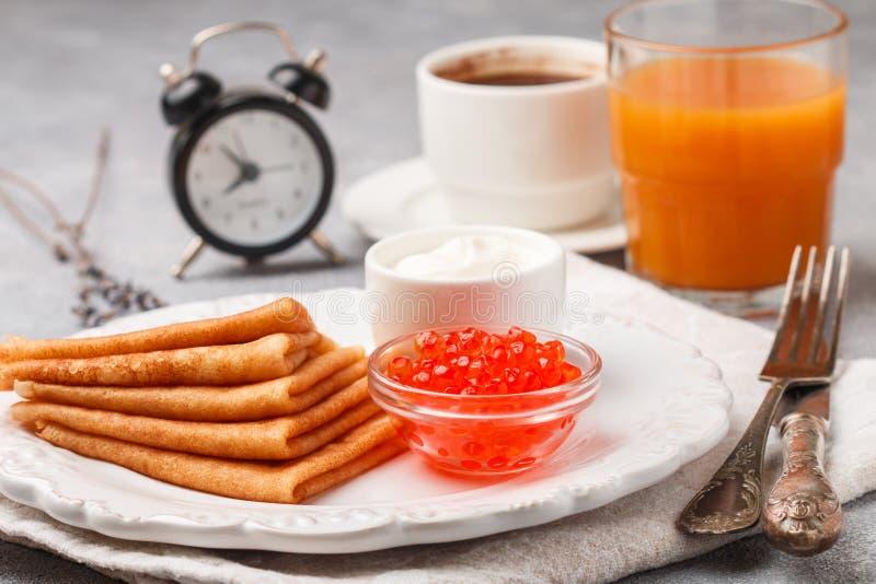 Frukostera tunna pannkakor med den röda kaviaren i den vita bunken royaltyfri foto