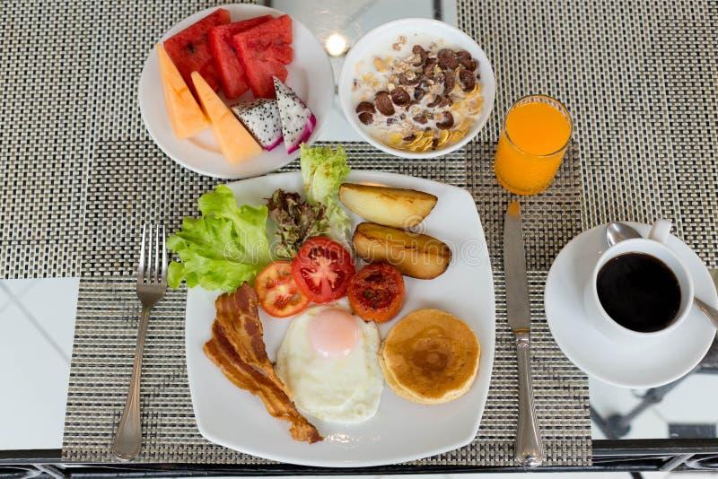 Frukostera uppsättningen på tabellen med pannkakor, bacon, ägg och kaffe arkivbilder