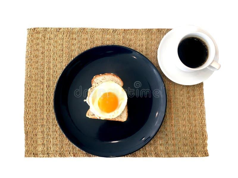 Frukostinställning med varmt svart kaffe och stekte ägget som överträffar på mattt pålagt sugrör för wholewheatbröd royaltyfri bild