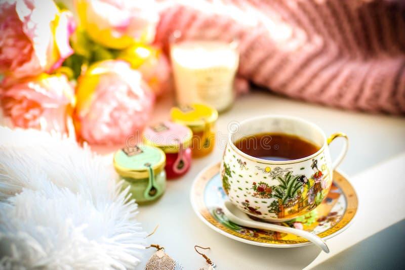 Frukostsammansättning Kopp tedriftstoppblommor och stearinljus royaltyfria bilder