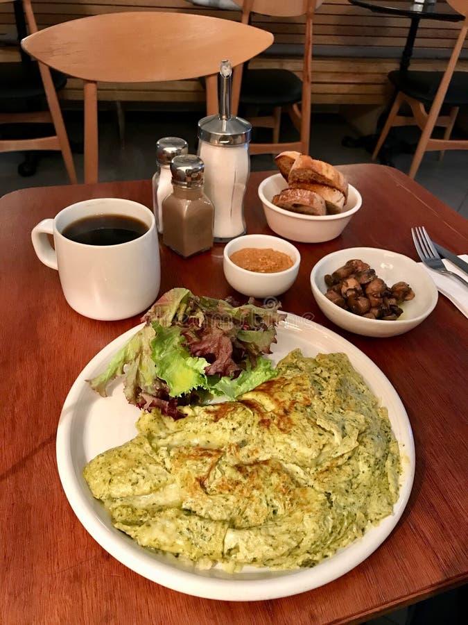 Frukosttabell med Pestoomelett, champinjoner, jordnötsmör och det nya filtret/filtrerat kaffe på restaurangen arkivfoton