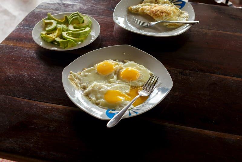 Frukosttabell med platta stekte ägg, förvanskade ägg och avocad arkivfoto