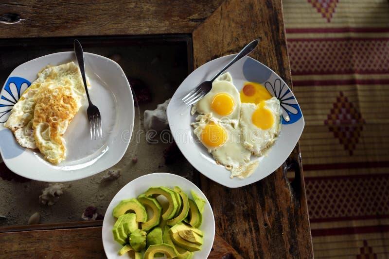 Frukosttabell med platta stekte ägg, förvanskade ägg och avocad royaltyfria bilder