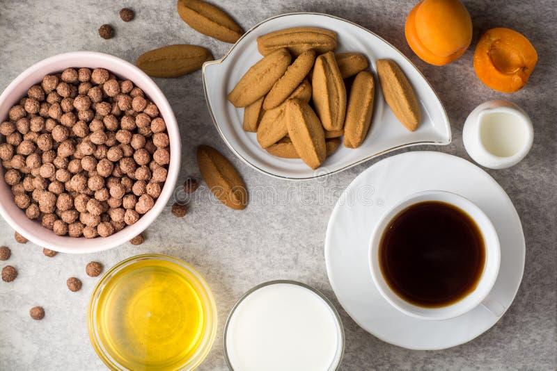 Frukosttabellen med kaffe, ljust rödbrun kakor, chokladsädesslagbollar, mjölkar, honung och aprikors på stenbakgrund arkivbilder