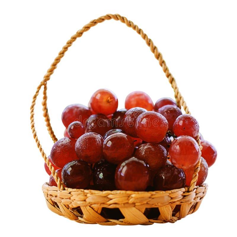 Frukt för röd druva i korgen som isoleras på vit bakgrund arkivfoto