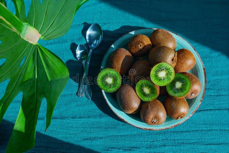 Frukt för tabell för maträtt för platta för sked för kiwimonsteragräsplan tropisk att lämna blå trämassa arkivfoton