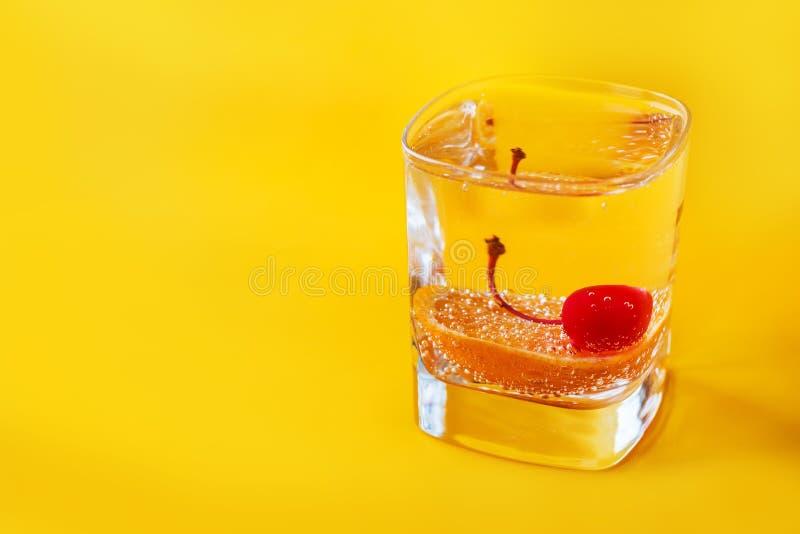 Frukt i ett exponeringsglas med sodavattenvatten arkivfoto