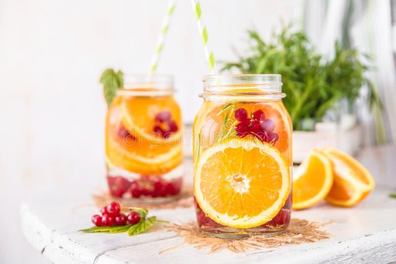 Frukt ingav Detoxvatten med orange röda vinbär och rosmarin arkivbild
