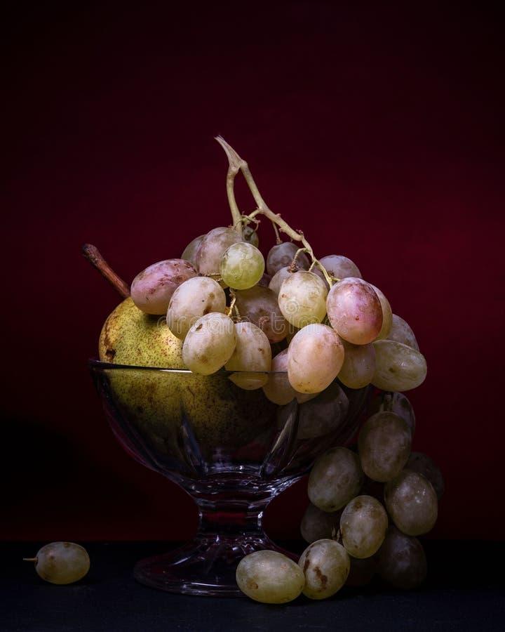 Frukt läcker bunke för päron för stillebenmatdruvor arkivfoto