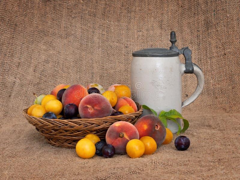 Frukt och öl Gammalmodig frukt från en lång övergiven fruktträdgård med den gamla ölölkruset 1 livstid fortfarande arkivfoton