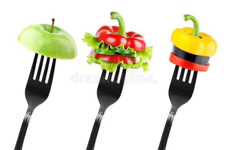 Frukt- och grönsakskivor på gaffel arkivbild