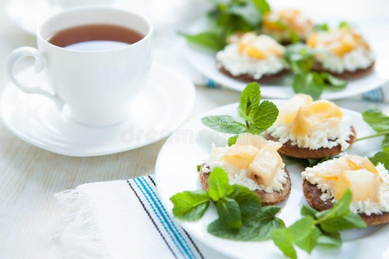 Frukt- och kesoefterrätt och en kopp av tea royaltyfri fotografi