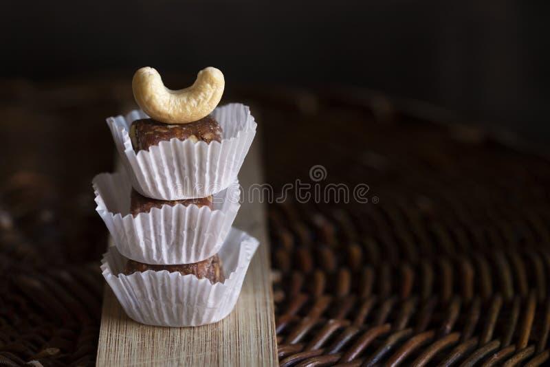 Frukt och tokiga godisstänger i pappers- former med den hela kasjun på överkanten på träbräde och det vide- magasinet arkivfoton