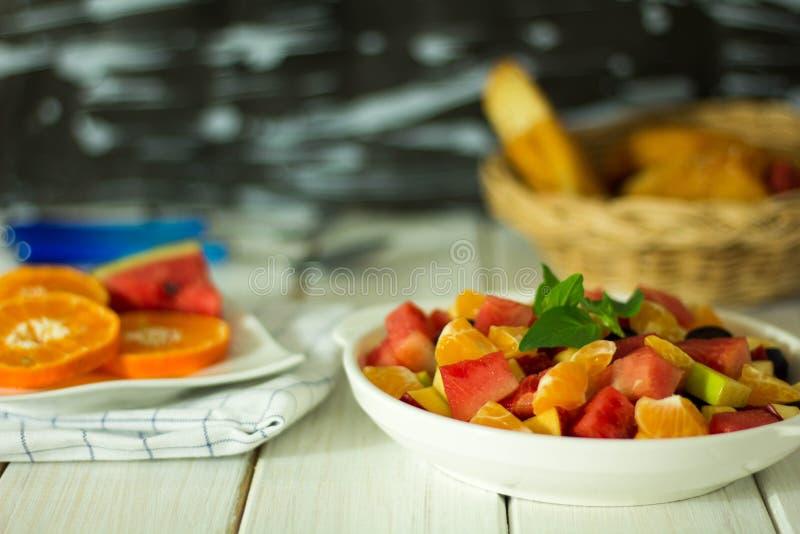 Frukt och vegetabldsallad förläggas på plattan arkivbilder