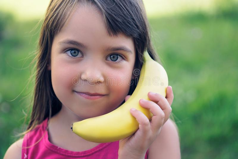 Frukt- skvallrar Hållande banan för härlig ung flicka som en telefon royaltyfria bilder