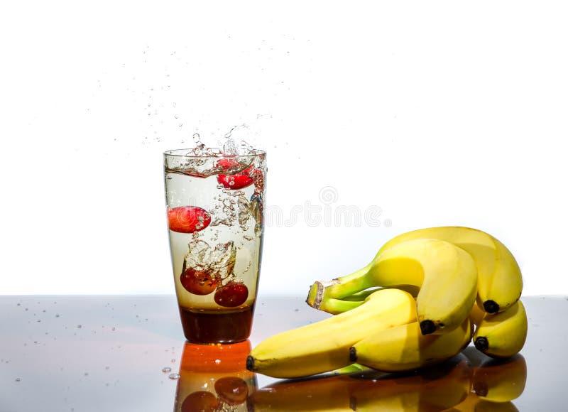 Frukt som plaskar i exponeringsglas av vatten royaltyfri foto