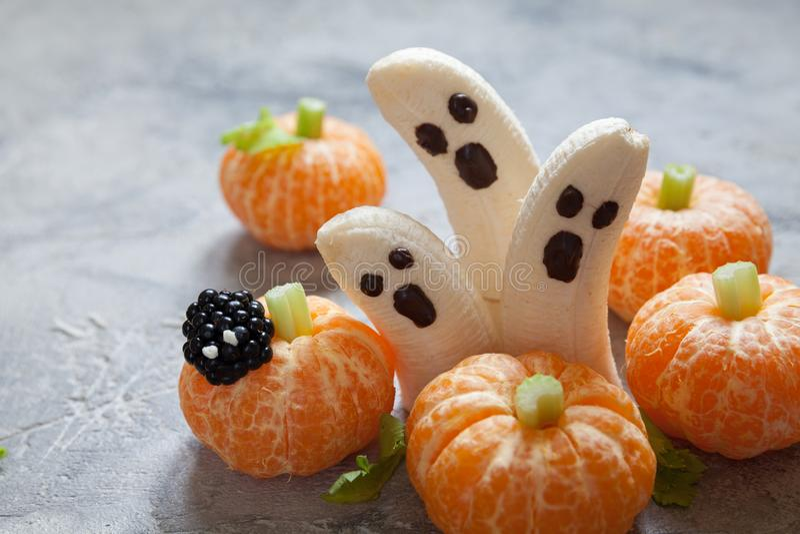 Fruktallhelgonaaftonfester Bananspökar och Clementine Orange Pumpkins royaltyfri foto