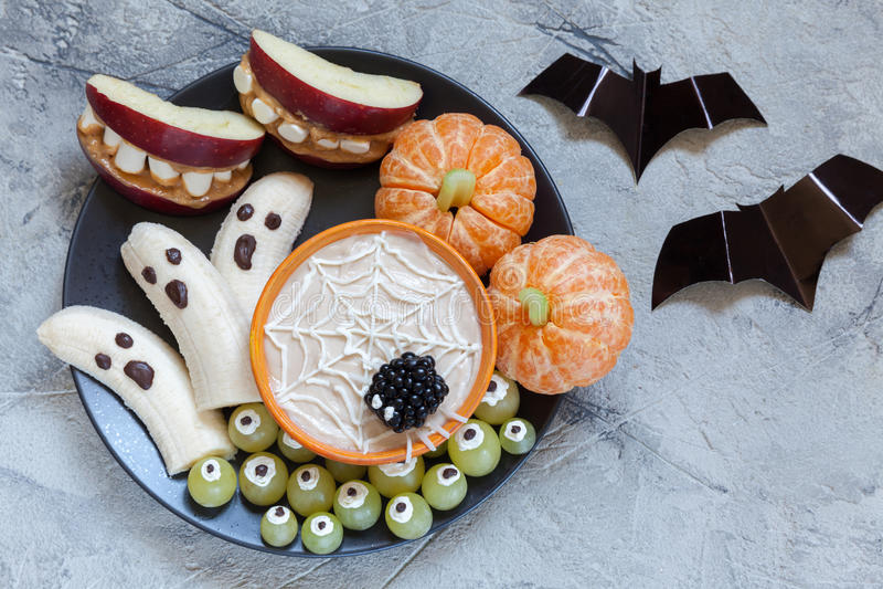 Fruktallhelgonaaftonfester Bananspökar och Clementine Orange Pumpkins, Apple monstermonteringar och spindelrengöringsduk royaltyfria foton