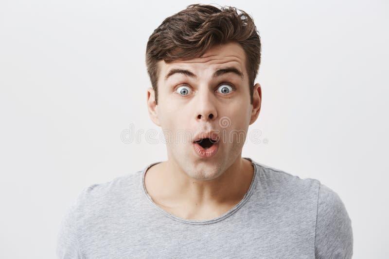 Fruktansvärd fel-synad ung caucasian snygg man i tillfällig kläder som skriker i chock som håller munnen öppen, känsla arkivbild