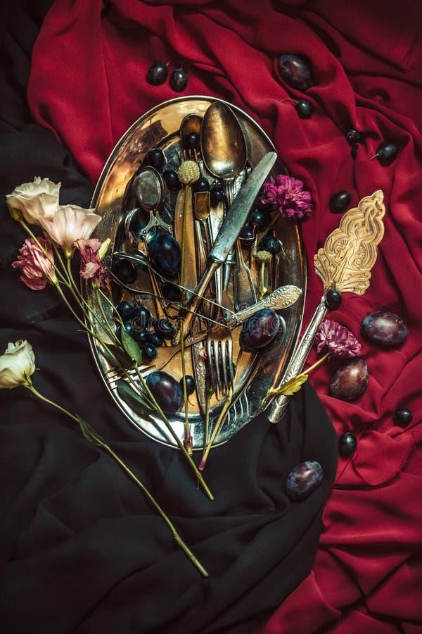 Fruktbunken med druvor och plommoner i silverplattan arkivbild