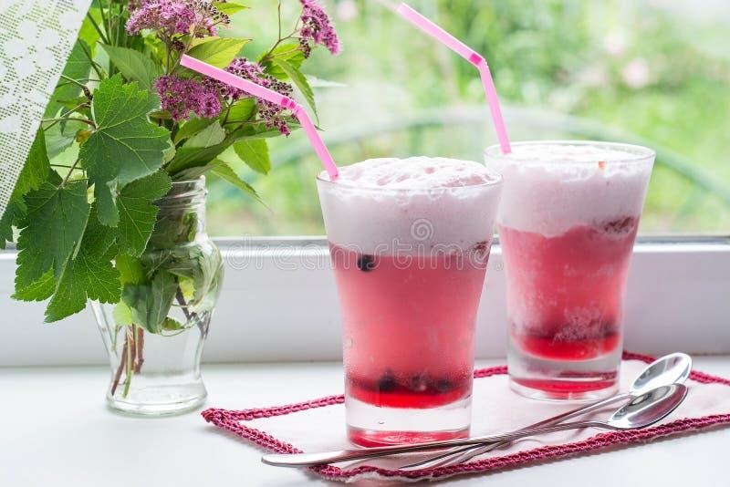 Fruktcoctail med glass och blommor på fönstret royaltyfria bilder