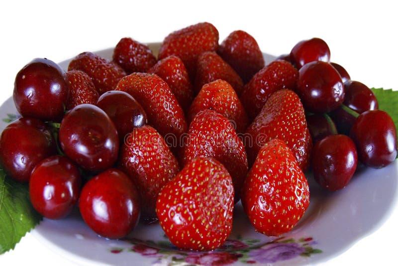 Fruktefterrätt från jordgubbar och söta körsbär arkivfoto