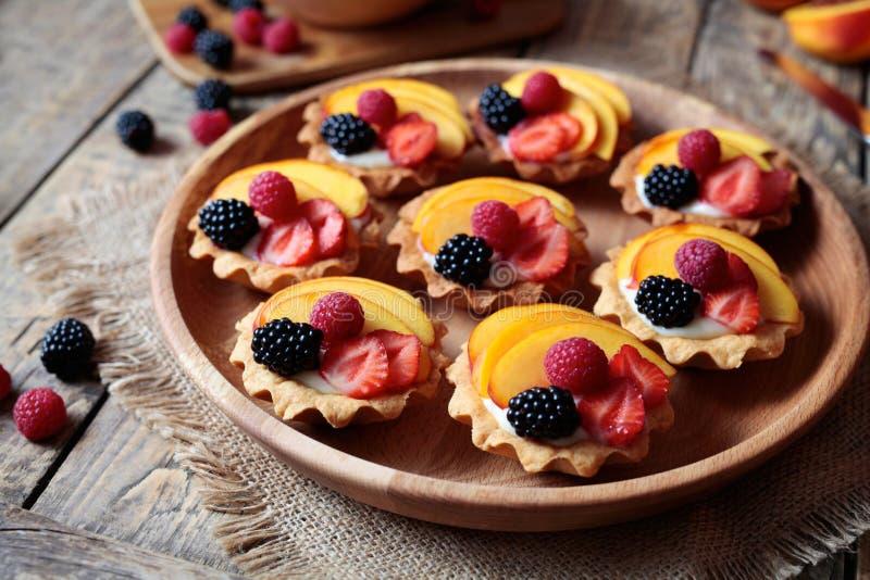 Fruktefterrätttartlets med vaniljvaniljsås och nya hallon, björnbär, persika Mörk lantlig stil royaltyfria bilder