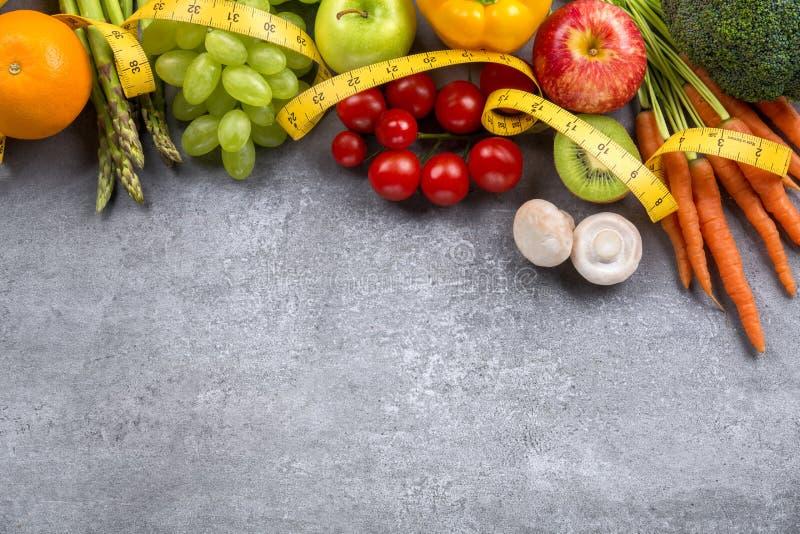 Frukter, grönsaker och måttbandet bantar in arkivfoto