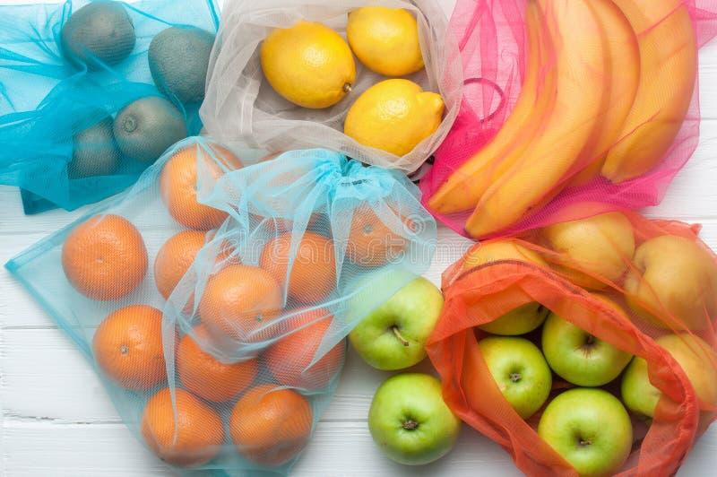 Frukter i eco-vänskapsmatch shoppingpåsar på vit träbakgrund royaltyfri fotografi