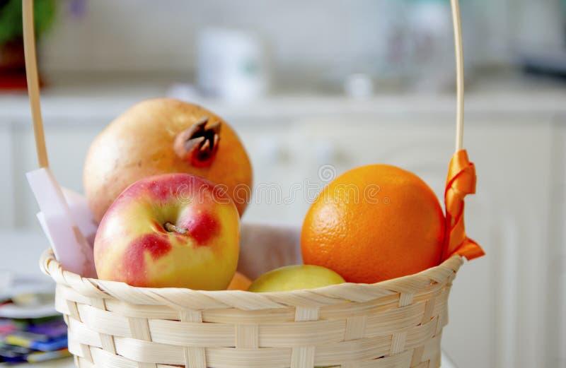 Frukter ligger i en vide- korg i det ljusa köket fotografering för bildbyråer