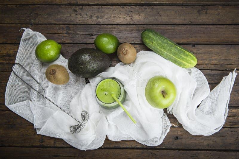 Frukter och grönsaker med ett exponeringsglas av den gröna smoothien arkivbild