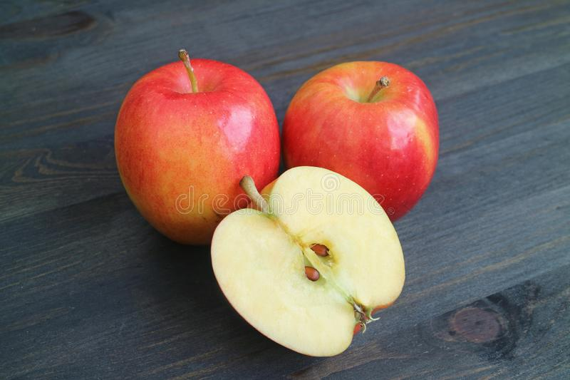 Frukter och tvärsnitt för vibrerande rött äpple hela på den mörka kulöra trätabellen royaltyfria bilder