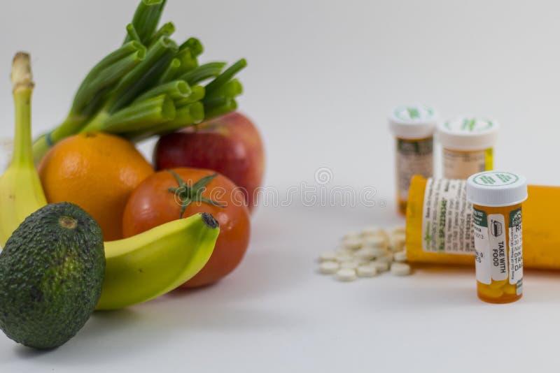Frukter och veggies och preventivpillerar arkivbild
