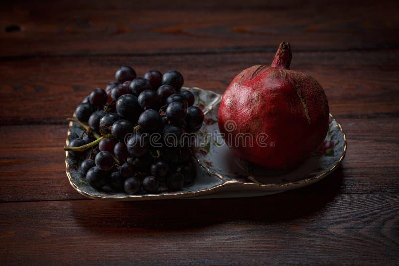 Frukter på en platta, druvor och granatäpplet arkivfoto