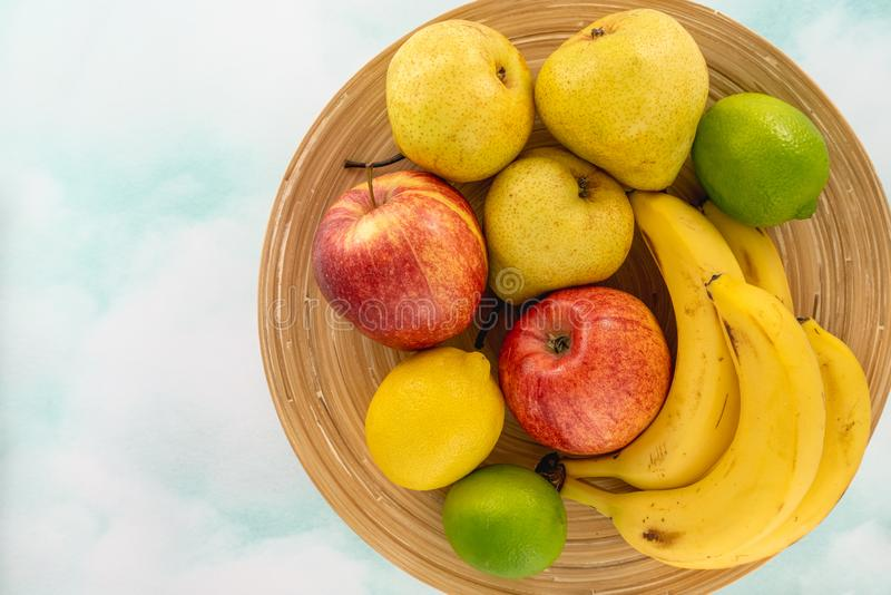 Frukter p? en pl?tera Äpplen, päron, bananer, citron och limefrukter B?sta sikt, kopieringsutrymme arkivbilder