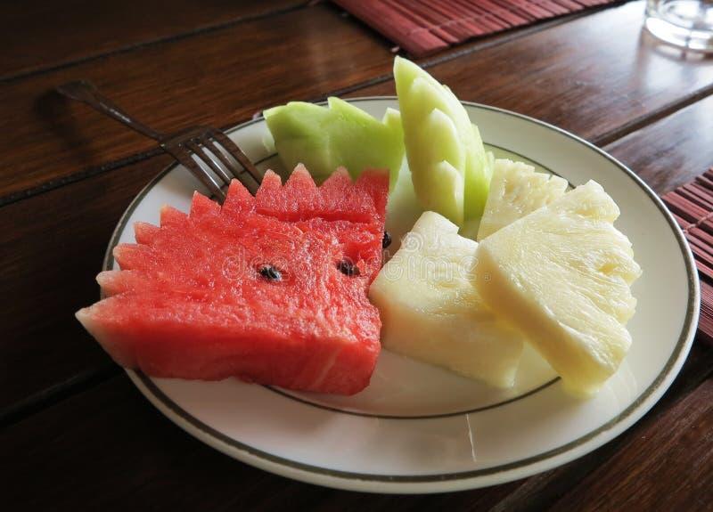 Frukter pläterar med den skivad melon, vattenmelon och ananas arkivfoton