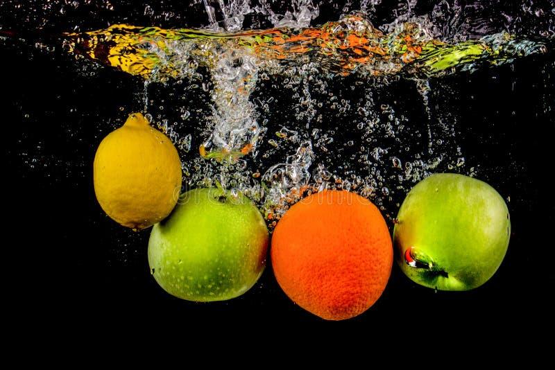 Frukter svävar i vatten med bubblor, är isoleras frukten i vattenfärgstänk och på en svart bakgrund arkivfoton
