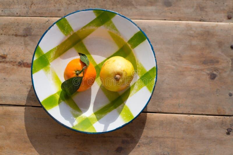 Frukter tangerin och päron i platta för tappningporslinmaträtt royaltyfri bild