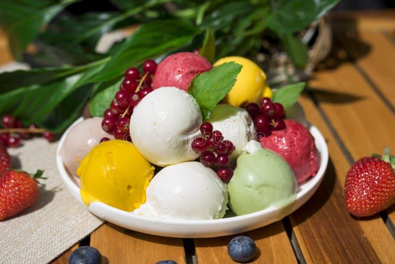 Fruktglassskopor som ?r ?ver huvudet p? den vita plattan med stycken av frukter och b?r som tj?nas som med flera f?rgrika skedar arkivfoto