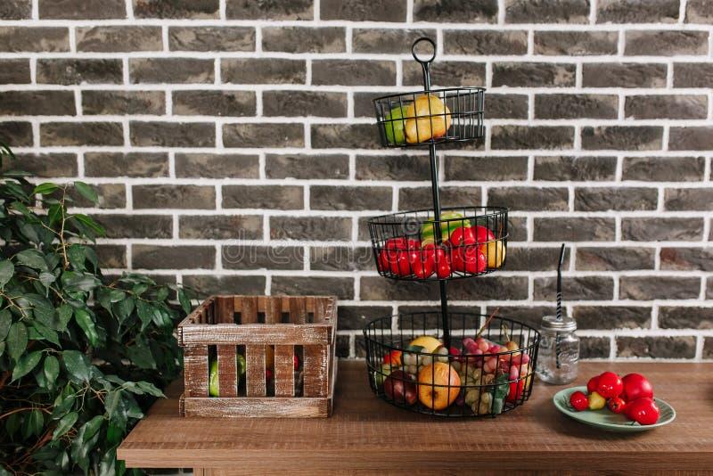 Fruktkorg i vindstilkök med bakgrund för tappningtegelstenvägg royaltyfri bild