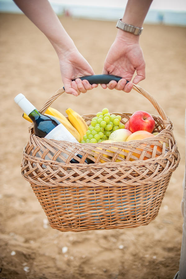 Fruktkorg och vin i händerna royaltyfri fotografi