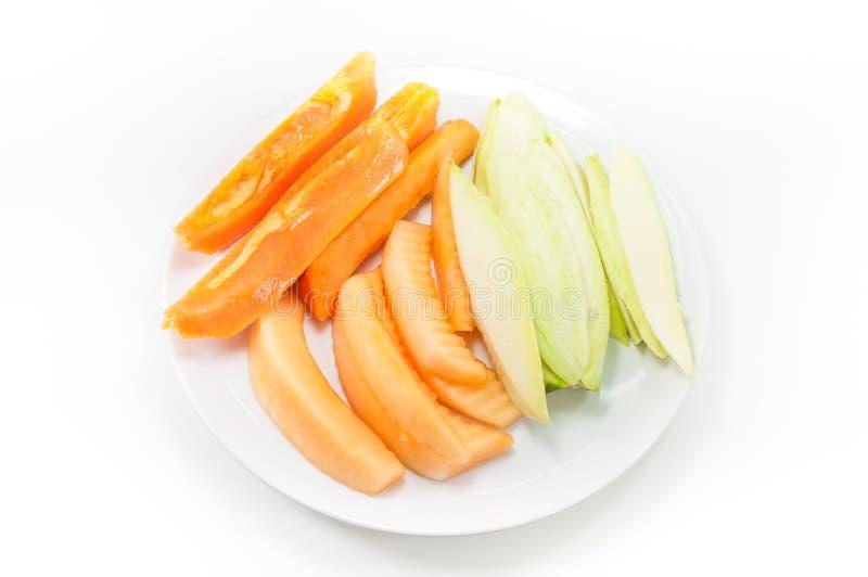 Fruktpapayamango och cantaloupmelon på maträtt på vit arkivbild