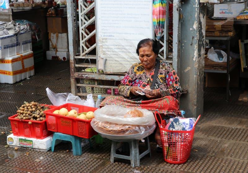 Fruktsäljaren som räknar pengar på den centrala marknaden, en stor marknad med otaligt, stannar av gods arkivfoto