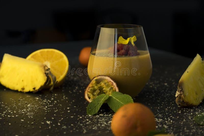 Fruktsaft för smoothie för fruktcoctail i ett genomskinligt exponeringsglas på tabellen, apelsinerna och tangerina med ananas och arkivfoton